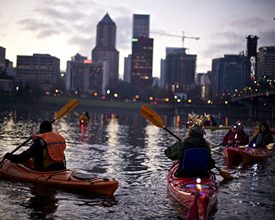 Kayakers take to the Willamette River at dusk.